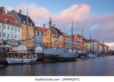 Copenhagen, Denmark - November 18 2017: Golden sunlight on the colourful waterfront of Nyhavn Canal (New Harbour), an entertainment and tourist district of Copenhagen.