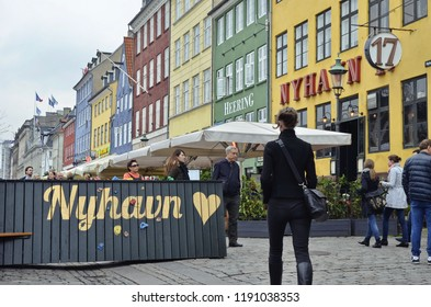 Copenhagen, Denmark - October 1, 2017:The crowded Nyhavn canal with the Heering and the Nyhavn 17 buildings and a wooden sign showing a golden heart, under the winter sky.