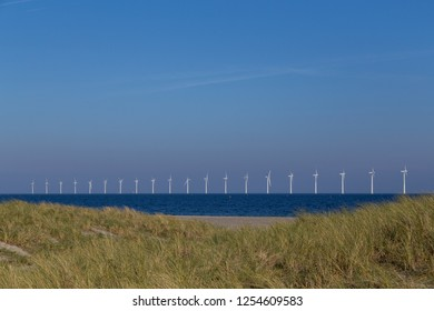 Copenhagen, Denmark - October 11, 2018: Sand dunes at Amager Beach with offshore wind power plants in the background