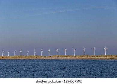 Copenhagen, Denmark - October 11, 2018: Amager Beach Park with row of offshore wind power plants in the background