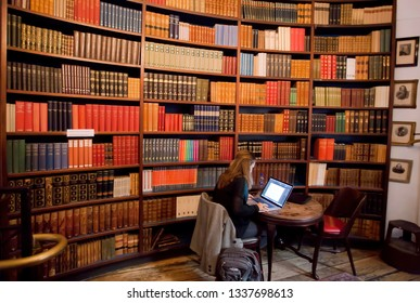 COPENHAGEN, DENMARK - SEPT 4: Bookstore with student working under laptop, and many vintage science books on shelves on 4 September, 2018. Copenhagen has 94,000 students enrolled in universities