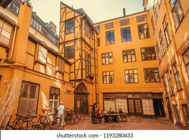 COPENHAGEN, DENMARK - SEPT 5: Young women sitting and relaxing on bench inside historical courtyard of traditional style house on 5 September, 2018. Copenhagen has population near 1.3 million