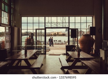 COPENHAGEN, DENMARK - SEPT 7: Bar interior with wooden tables and opened door to riverbanks by danish capital on 7 September, 2018. Copenhagen has population near 1.3 million