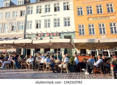 COPENHAGEN, DENMARK - SEPT 7: People sitting at outdoor restaurants of Nyhavn, eating and drinking outside in popular leisure area on 7 September, 2018. Copenhagen has population near 1.3 million