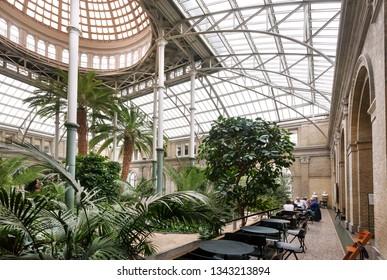 COPENHAGEN, DENMARK - SEPT 7: Winter garden with restaurant and exotic trees inside New Carlsberg Glyptotek historical museum on 7 September, 2018. Glyptotek has collections with 10,000 works of art.