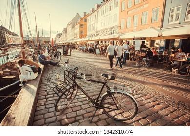 COPENHAGEN, DENMARK - SEPT 8: Evening sun on Nyhavn riverbank with walking people, and relaxing in restaurants of popular city leisure area on 8 September, 2018. Copenhagen has population 1.3 million