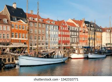 COPENHAGEN, DENMARK - SEPT 8: Riverboats, yachts and historical area of Nyhavn with outdoor restaurants of danish capital on 8 September, 2018. Copenhagen has population 1.3 million