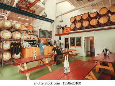 COPENHAGEN, DENMARK - SEPT 9: Barrels with beer and some customers inside the craft bar on 9 September, 2018. Mikkeller is a microbrewery founded in 2006