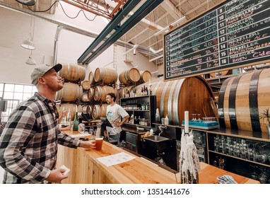 COPENHAGEN, DENMARK - SEPT 9: Customer of craft beer bar making choice at bar counter and buying a drink on 9 September, 2018. Mikkeller is a microbrewery founded in 2006