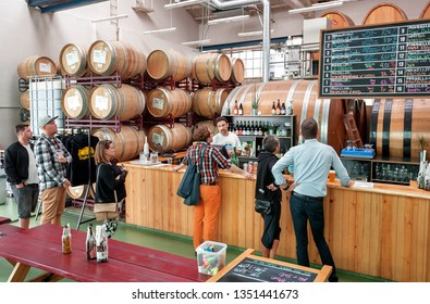 COPENHAGEN, DENMARK - SEPT 9: Customers of craft beer bar with barrels and urban interior making choice at bar counter on 9 September, 2018. Mikkeller is a microbrewery founded in 2006