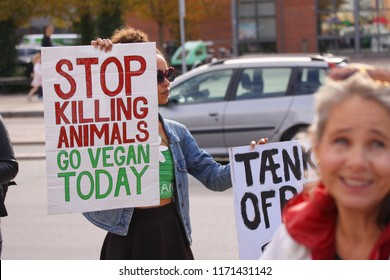 Copenhagen, Denmark - September 1, 2018: Vegan woman of mixed race protesting against cruelty to animals and eating meat with sign saying stop killing animals go vegan today