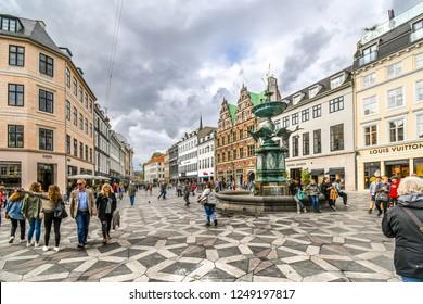 Copenhagen, Denmark - September 10 2018: Tourists wander the Stroget shopping district near the Stork Fountain, the longest pedestrian street in the world, in Copenhagen, Denmark.