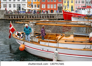 Copenhagen, Denmark - September 10 2018: A senior man and woman walk on the deck of their sailboat as they dock in front of tourists and cafes on the colorful Nyhavn canal in Copenhagen, Denmark.