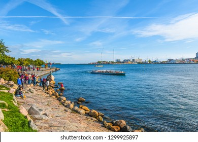 Copenhagen, Denmark - September 12 2018: Tourists on holiday visit the Little Mermaid statue on the Langelinie promenade in Copenhagen, Denmark as a tour boat float by.