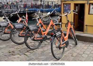 Copenhagen, Denmark - September 15, 2018: Orange bicycles parked beside the canal in Copenhagen, Denmark.