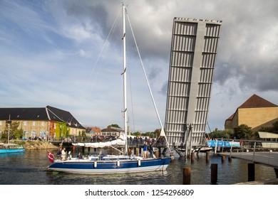 Copenhagen, Denmark - September 2, 2017: A sailboat passes an open drawbridge in Christianshavn district