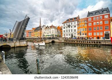 Copenhagen, Denmark - September 23 2018: The Nyhavn bridge opens to let a small sailboat through the canal in the waterfront tourist area of Nyhavn in Copenhagen, Denmark.