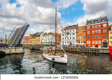 Copenhagen, Denmark - September 23 2018: The Nyhavn bridge opens to let a small sailboat through the canal in the waterfront tourist area of Nyhavn in Copenhagen, Denmark.