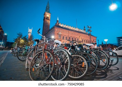 Copenhagen, Denmark, September 26, 2015: View of a bicycle parking lot with a lot of bicycles in the square at the city hall at dusk, blurry dynamic photo, selective focus