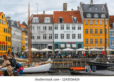 Copenhagen, Denmark - September23 2018: Tourists pose for photos and dine at sidewalk cafes on an overcast autumn day on the 17th century waterfront canal Nyhavn in Copenhagen, Denmark.