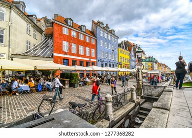 Copenhagen, Denmark - September23 2018: Tourists sightsee, shop and dine at sidewalk cafes on an autumn day on the 17th century waterfront canal Nyhavn in Copenhagen, Denmark.