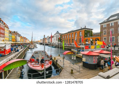 Copenhagen, Denmark - September23 2018: Tourists sightsee, board guide boats and dine at sidewalk cafes on an autumn day on the 17th century waterfront canal Nyhavn in Copenhagen, Denmark.