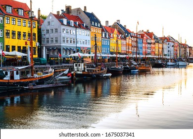Copenhagen, Denmark. View of famous Nyhavn area in the center of Copenhagen, Denmark at night. Various boats moored with historical buildings and cloudy sunset sky