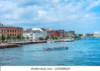 Copenhagen harbor view, boat with tourists and modern city skyline in sunshine weather with cloudy sky, Denmark