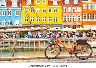 Copenhagen iconic view. Orange bike against famous old Nyhavn port in the center of Copenhagen, Denmark during summer sunny day