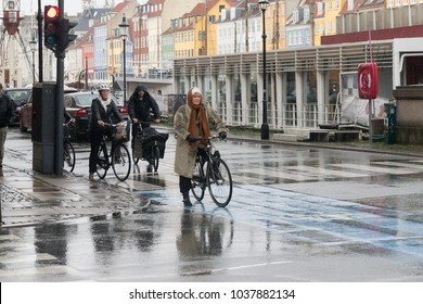 Copenhagen - October 23, 2016: An old lady and other people on their bycicles waiting to cross the street during a rain in Nyhavn.