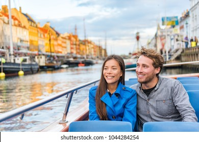 Copenhagen tourists people on Denmark travel holiday cruise boat tour in old port. Young multiracial couple travelers relaxing enjoying view of Nyhavn danish destination in Europe, fall or spring.