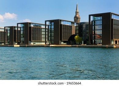 Copenhagen Waterfront modern buildings with a medieval church tower peeping up behind.