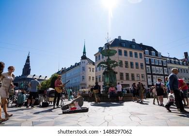Copenhagen, Zealand / Denmark - August 24 2019: Kongens Nytorv in Copenhagen filled with people, sculptures, and street musician