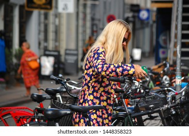 Copenhagen/Denmark - 17 June 2019: Many bicycles in street, bicycle parking.  Girl in a bicycle parking.