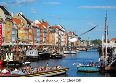 Copenhagen/Denmark - 17 June 2019: Tourists sightseeing cruising on boat by Nyhavn embankment, with colorful buildings in background in Copenhagen.
