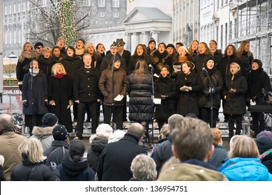 COPENHAGEN,DENMARK - November 17: a choir sings Christmas carols on a square in the city center, by-standers gathered in front of the stage, in 2012