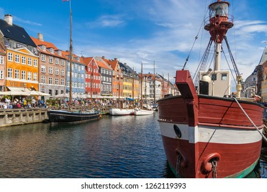 Copenhagen/Denmark-July 26, 2018 Old wooden ships, colorful houses and a street full of tourists in Nyhavn. Nyhavn is a 17th century harbor district in the center of Copenhagen.