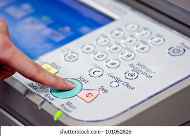Copier Start - Finger pressing the start button on a multifunction printer or copier.