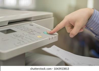 Copier Start, Finger pressing the start button on a multifunction printer or copier
