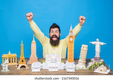 Copies of famous monuments of world, grouped together. Worlds monuments, architectural landmarks, miniature concept - happy bearded man raised his hands up near table with model miniature buildings.