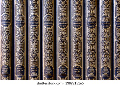 """Copies of the Holy Qu'ran on shelves in a Mosque. with """"The Noble Qur'an.  English translation of the meanings and commentary"""" in English and Arabic."""