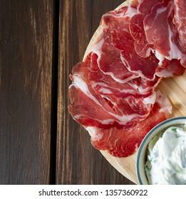 coppa di parma meat, cream cheese and ciabatta bread on wooden surface
