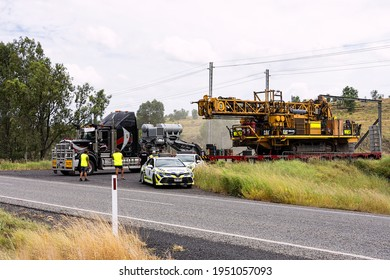 Coppabella, Queensland, Australia - 26 February 2021:Large load of mining machinery on a semitrailer about to enter onto the highway under police escort at Coppabella, Queensland, Australia.