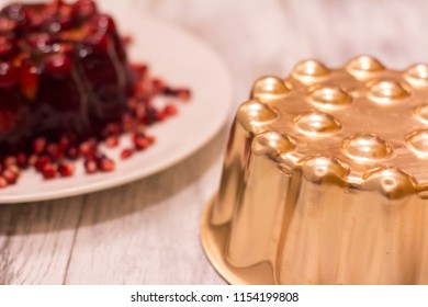 A copper baking mold and a decorative cranberry dessert with pomegranate seeds on a white plate and wooden table backdrop
