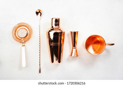 Copper bar tools and accessories for making cocktail. Shaker, jigger, strainer, spoon, tongs, muddler. Alcohol drink and beverages preparation concept. White background, top view, copy space