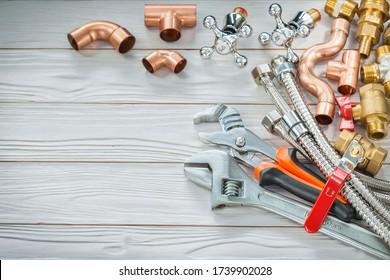Rohrformstücke aus Kupfer und Messing für Verbindungsleitungen und verstellbare Armreifen auf Holzplatten aus Vintage