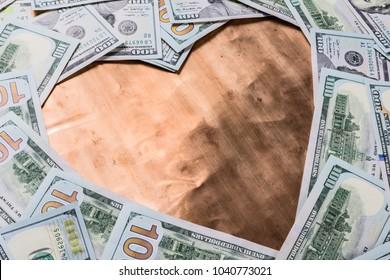 Copper bronze heart shape in center of dollar money background