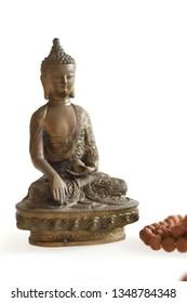 Copper Buddha statue on a white background and Rudraksha mala