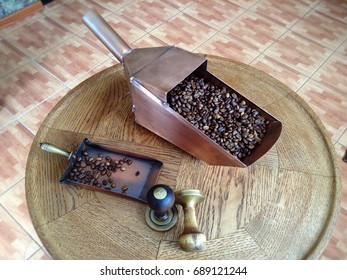 Copper coffee scoop with coffee beans and coffee tamper on a wooden table