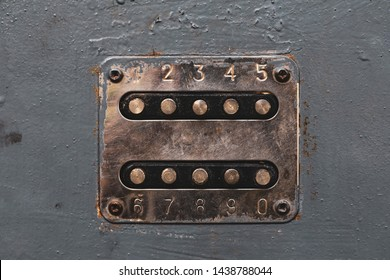 Copper color number buttons to unlock the door lock. Cupreous panel with numbers on the old metal door. Unlocker buttons on metal door. Steel numeric keyboard on vintage wall, entry.